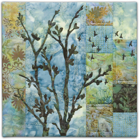 Quilt block with stylized tree and flock of birds flying in blue, yellow, and green floral patterns