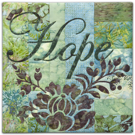 "Quilt block with the word ""Hope,"" stylized flowers and a catepillar in purple, blue, and green floral patterns"