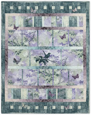 Pieced quilt pattern with stylized birds and butterflies, in pink, purple, and teal