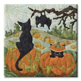 Quilt block of two black cats in a pumpkin patch, with a bat hanging from a tree and the large moon behind.