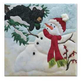 Quilt block of a snowman melting on a bright day, with a bear in a tree