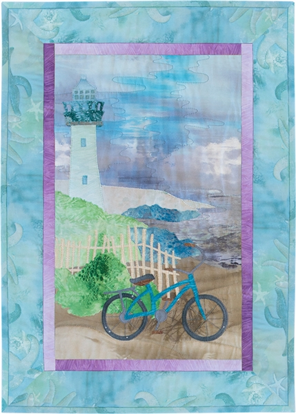 Quilt block of a bicycle leaning on a white picket fence, with a path leading up to the lighthouse that overlooks the ocean.