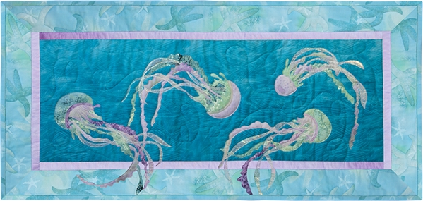 Quilt block of jellyfish dancing under the waves.