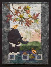 Quilt block of a black cat with white nose, paws, and chest under an Autumnal maple branch looking at a bird, while another bird sits on his back