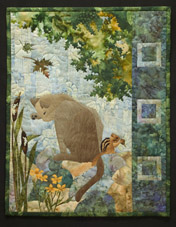 Quilt block of a brown cat rubbing his face, while leaves fall overhead and a chipmunk eats an acorn.