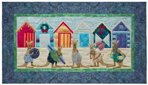 Quilt block of five kangaroos ready to play on the beach, in front of brightly colored beach huts decorated for the holidays.