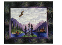 Quilt block showing a fisherman standing in a river casting a fly, with an eagle flying overhead. The riverside cabin and large purple mountains are in the background.