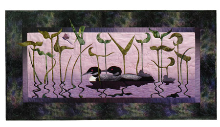 Quilt block of two loons swimming together at dusk in the reeds.