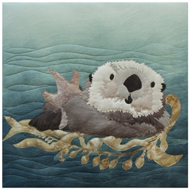 Quilt block of an otter swimming with a snack on her tummy.