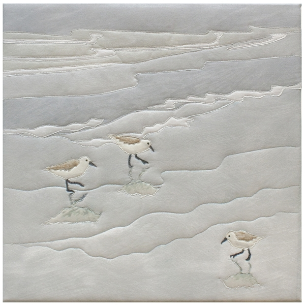 Quilt block of sandpipers looking for food on a beach.
