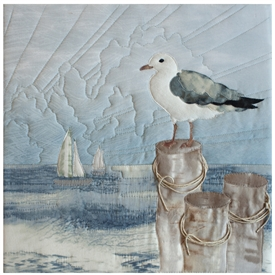 Quilt block of a seagull perched on a post overlooking the ocean to get the best perspective.