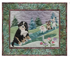 Quilt block of a Saint Bernard playing on the seesaw with three smaller dogs.