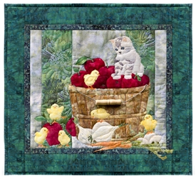 Quilt block showing a kitten watching over some new chicks, while perched on a bushel of apples.