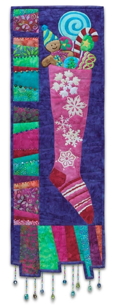 Quilt block of a Christmas stocking filled to the brim with candy and gingerbread cookies, with unique pieced border and dangling beaded accents