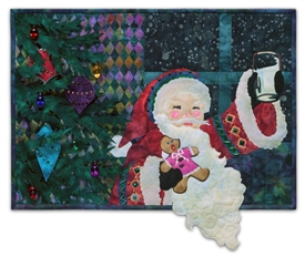 Quilt block of Santa in front of a decorated tree, raising a glass to the kind person that left him cookies and milk.