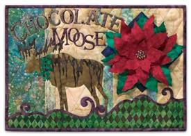 This quilt block is a play on words, as a moose drizzled with chocolate stands near a large, probably inedible, poinsettia.