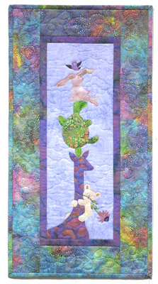 Quilt block of a giraffe holding up a turtle, a bunny, and a teddy bear, with a little bird flying above them