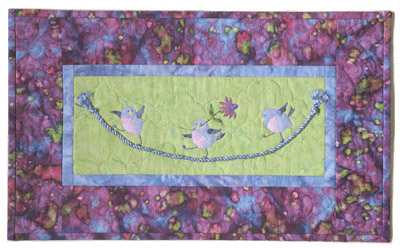 Quilt block of three blue birds swinging on a tight rope.