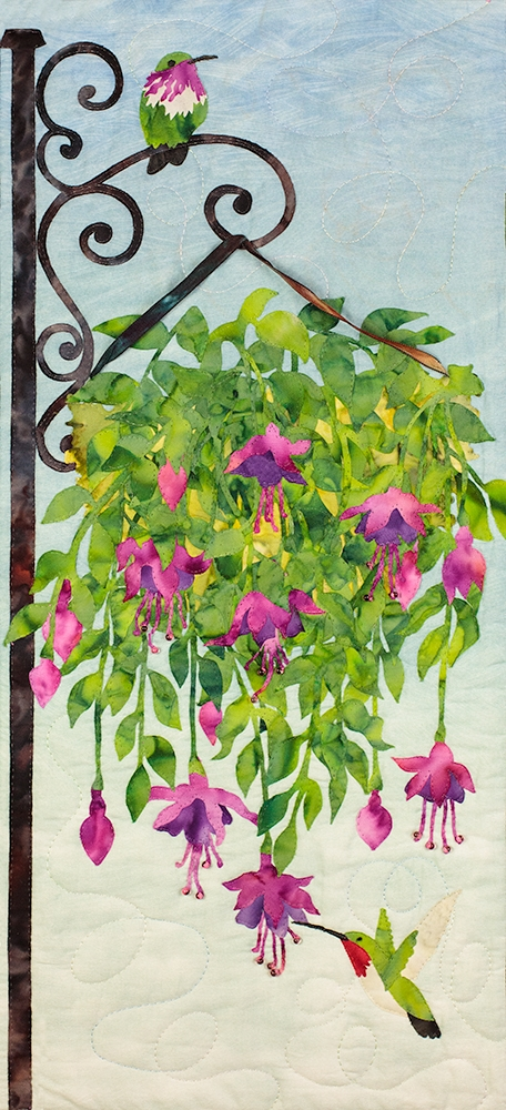 Fabric art print of hummingbirds drinking nectar from a hanging plant.