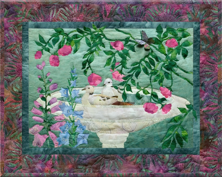 Quilt block of two birds making a splash in a bird bath.
