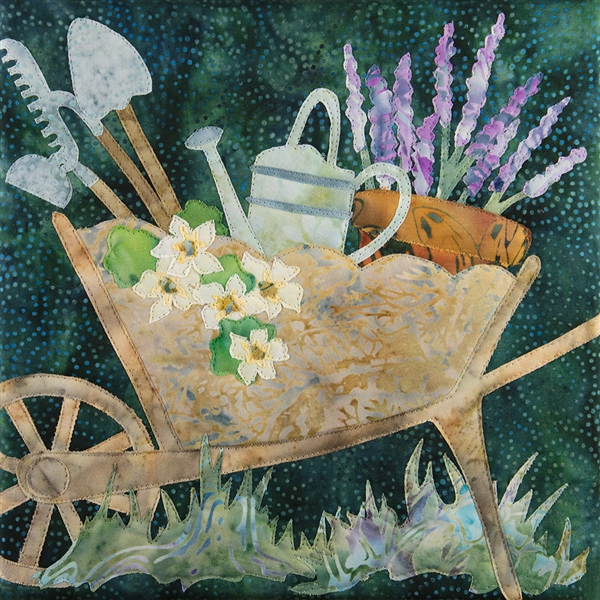 A quilt block featuring a wheel barrow full of gardening tools, flowers and a pot full of lavender.