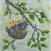A quilt block with two baby yellow birds snuggled into their nest up in a leafy tree branch