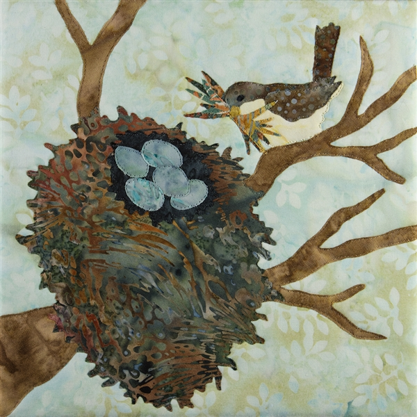 Quilt block with a bird returning to its nest snuggled in tree branches where 5 blue eggs lay