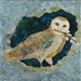 Quilt block with an owl holding pussy willow stems on a blue background