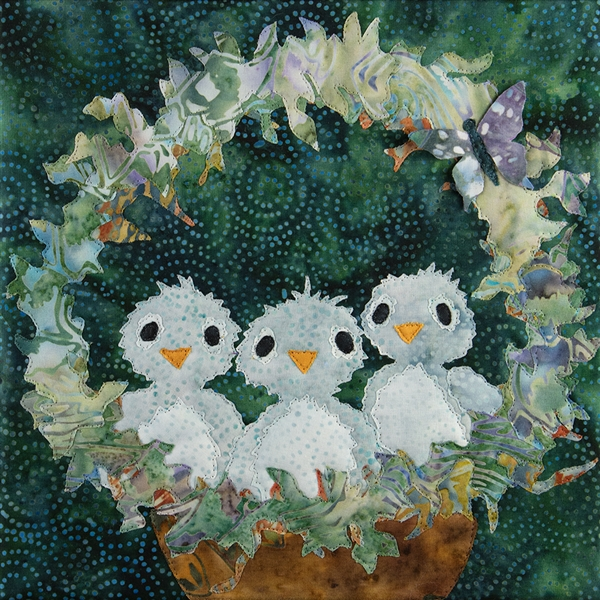 A quilt block with three baby blue birds sitting in their nest with sweet expressions on their faces. A little butterfly is on the arch over the nest.