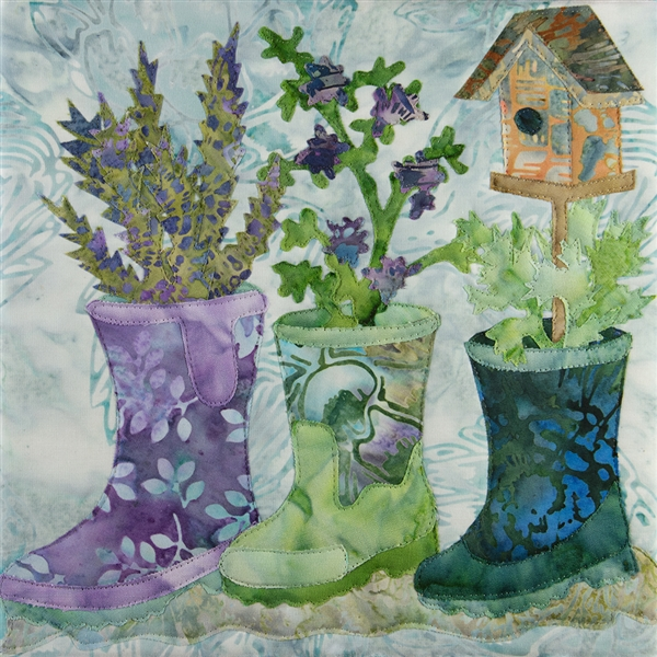 A quilt block with three rain boots that have been converted into planters. One boot also has a bird house on a stand coming out of it