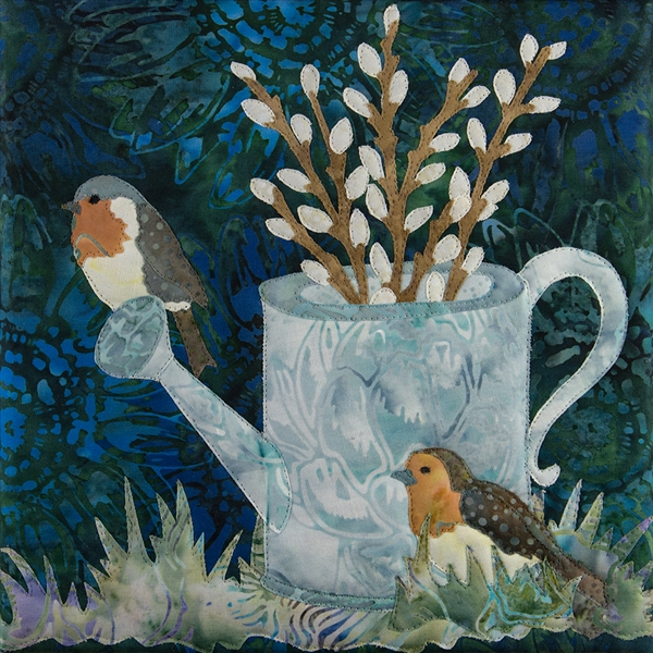 a quilt block with two speckled birds sitting on a tin watering can that is nestled in the grass and full of pussy willow branches.