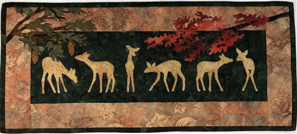 Quilt block of a group of deer graze peacefully under the trees
