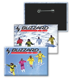 Lenticular button with orange and yellow snow skiiers jump off a mountain, flip