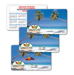 Lenticular calendar card with palm trees, umbrella, and lawn chair appear on a tropical Hawaiian beach, flip