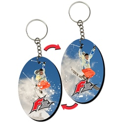 Lenticular foam key chain with oval shaped, snow skiier launches off a mountain into the crisp Alpine air, flip