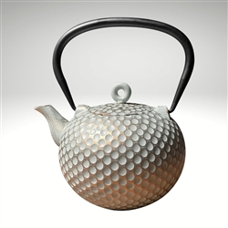 "Image of the ""Dim"" cast iron teapot by Ja by Frieling. This teapot has a textured and handpainted exterior in a gold and mint circle pattern. The image shows the black handle."