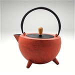 "Image of the ""Pop"" cast iron teapot by Ja by Frieling. This teapot has a textured and handpainted exterior in a gold and mint circle pattern. The image shows the black handle."