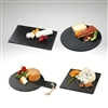 Image of all four serving board shapes, rectangular, round, square, and paddle with cheese and crackers on top of black slate.
