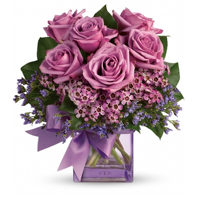 Shades of purple are in perfect harmony in this profoundly pretty arrangement. A lovely mix of classic and modern, ribbons and roses, it's sure to make someone's day!