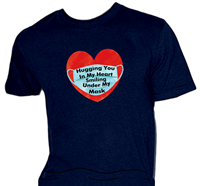 "Navy shirt has a washed-out red heart with a protective mask that says, "" Hugging You in My Heart...Smiling Under My Mask"""