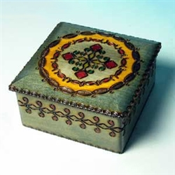 This square box is decorated with a circular pattern around a cross. Yellow, red, and green accents enhance the antiqued look of the box and a lip around the lid distinguishes the carving around the side of the box.