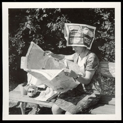 Relaxing in the park with her home made sun hat.  Ironic that the pictures on the hat are fashion photos.  Historical Black and White Photo Postcard