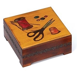 Sewing Box. This square box with feet features a sewing theme design featuring scissors, buttons, a thimble, a needle and thread with nice carved detail on three sides.  The inside bottom is lined with red felt.
