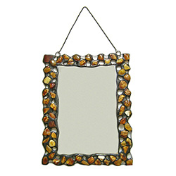 Hand made metal frame decorated with genuine natural amber stones.  There are three minor flaws in the mirror's edge so we are discounting.