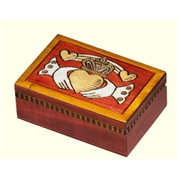 This box is decorated in warm colors with a claddaugh carved onto the lid of the box.