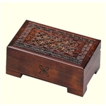 This dark box has a circular Celtic pattern with metal inlays and a detailed handcarved design on the lid. A removable drawer rests inside the box and the box has a footed base.