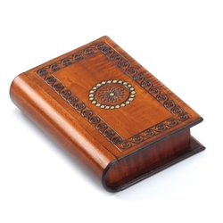 This trick box is shaped like a book and decorated with a spiral border pattern around a floral circle accented with gold paint. The binding of the book slides to reveal a removable panel allowing access to the box compartment.