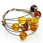 Eight beautiful strands of round amber beads in three shades on silver wire.  Each amber bead is separated by a silver sphere.