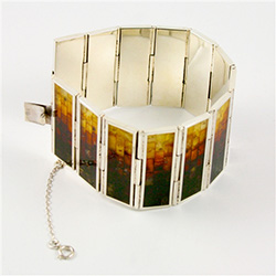 Hinged sterling silver cuff bracelet consists of 13 rectangular segments, inlaid with multi-color mosaic amber. The process to create this amber mosaic is quite unique.  See the video below.