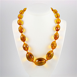 Stunning necklace composed of clear honey amber oval beads, faceted and graduated in size.  Each piece is separated by a smaller amber bead.